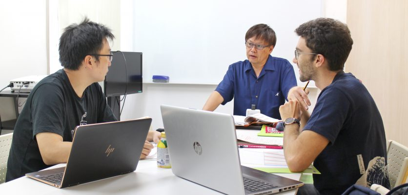A Japanese teacher giving Japanese lesson to two students